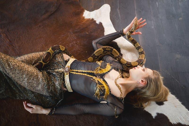 Giovane donna attraente che si trova sul pavimento con un serpente sul suo corpo fotografie stock