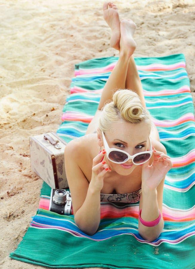 Giovane donna attraente che si trova sulla spiaggia con variopinto d'annata fotografia stock libera da diritti