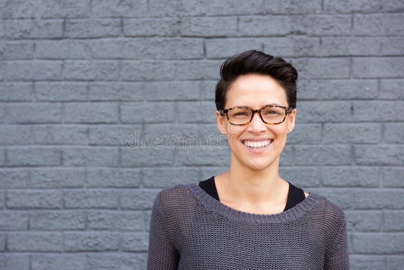 Giovane donna attraente che sorride con i vetri fotografie stock