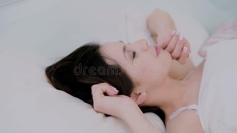 Giovane donna attraente che sveglia a letto a casa La ragazza guarda alla macchina fotografica ed ai sorrisi svegli Donna fresca  fotografia stock libera da diritti