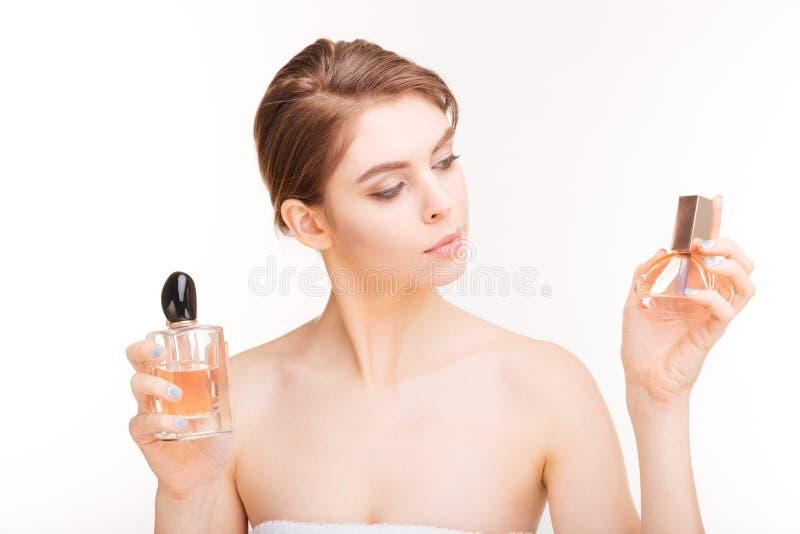 Giovane donna attraente che tiene due bottiglie dei parfums fotografia stock