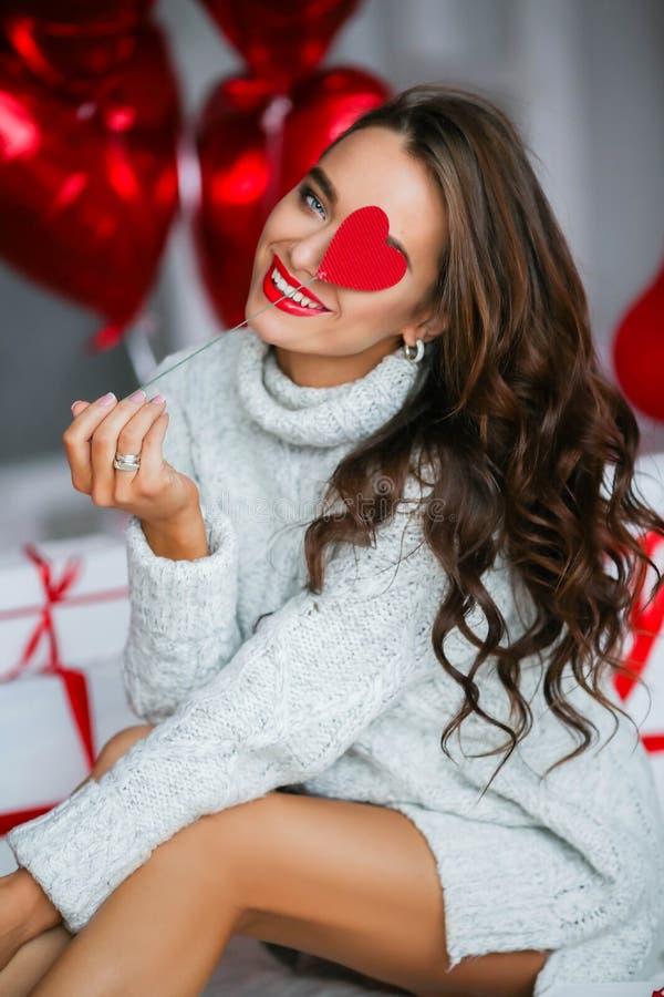 Giovane donna attraente con i regali ed i palloni fotografia stock