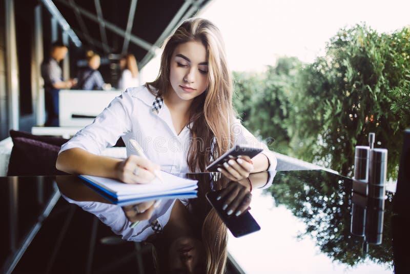 Giovane donna attraente con il bello fronte e sorriso che fa le note in taccuino, facendo uso del telefono cellulare per il proge immagine stock
