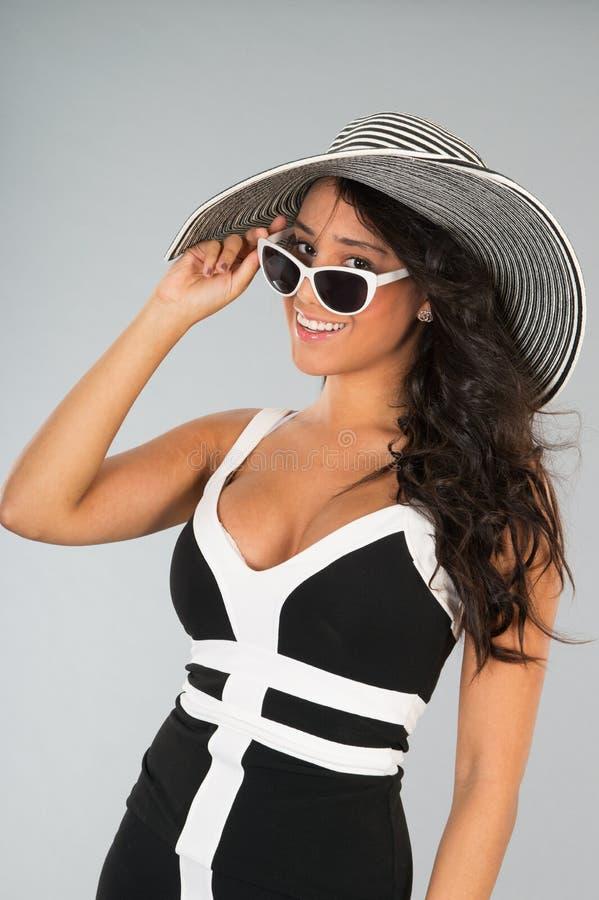 Giovane donna attraente con il cappello di paglia e gli occhiali da sole fotografia stock libera da diritti