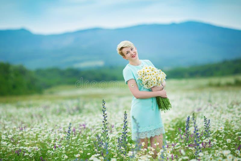 Giovane donna attraente con il mazzo della camomilla che cammina attraverso il campo della camomilla Aria aperta bionda attiva immagine stock