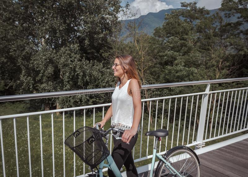 Giovane donna attraente con la bicicletta su un ponte fotografia stock