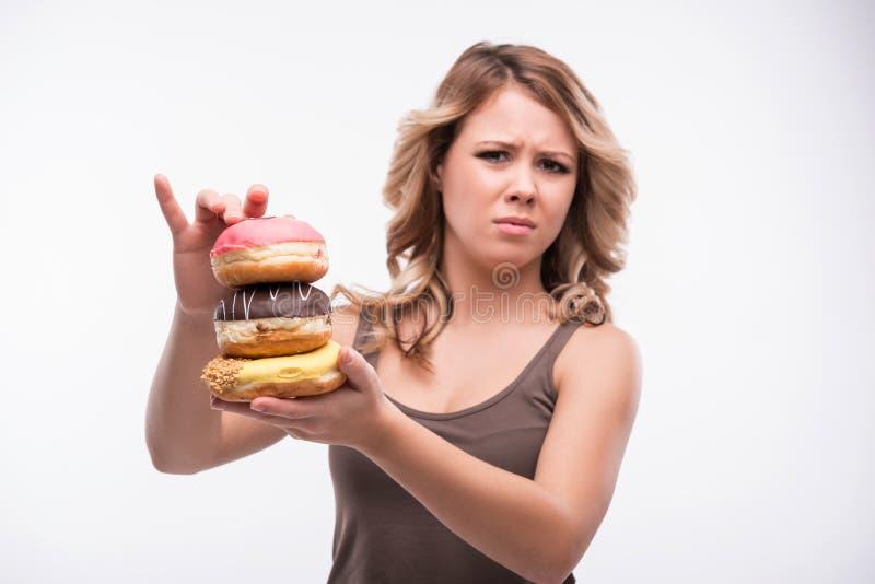 Giovane donna attraente con le ciambelle sopra fotografia stock libera da diritti