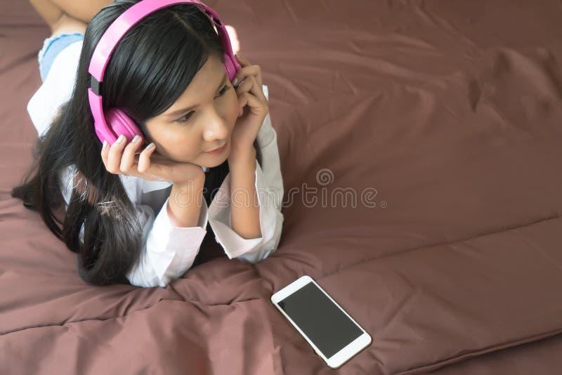 Giovane donna attraente con musica d'ascolto delle cuffie rosa sulla m. immagine stock libera da diritti