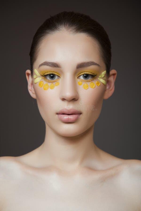 Giovane donna attraente con pelle pulita perfetta Petali dei fiori sul suo fronte Concetto di cura di pelle Fondo grigio Trucco d fotografie stock libere da diritti