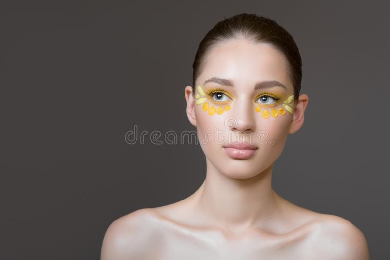 Giovane donna attraente con pelle pulita perfetta Petali dei fiori sul suo fronte Concetto di cura di pelle Fondo grigio Trucco d fotografia stock libera da diritti