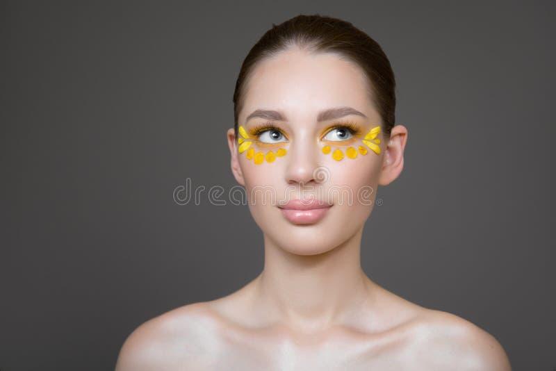 Giovane donna attraente con pelle pulita perfetta Petali dei fiori sul suo fronte Concetto di cura di pelle Fondo grigio Trucco d fotografie stock