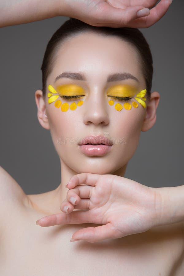 Giovane donna attraente con pelle pulita perfetta Petali dei fiori sul suo fronte Concetto di cura di pelle Fondo grigio Trucco d fotografia stock