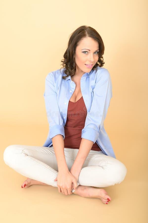 Giovane donna attraente contenta rilassata che si siede sul pavimento immagine stock