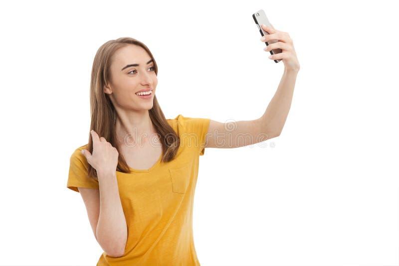 Giovane donna attraente del ritratto che fa la foto del selfie sullo smartphone isolato su un fondo bianco Derisione su immagine stock