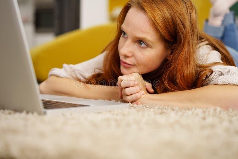 Giovane donna attraente della testarossa che per mezzo del suo computer portatile fotografia stock libera da diritti