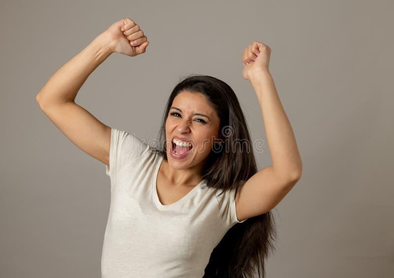 Giovane donna attraente emozionante ed euforica felice che celebra vittoria e successo dei soldi immagini stock