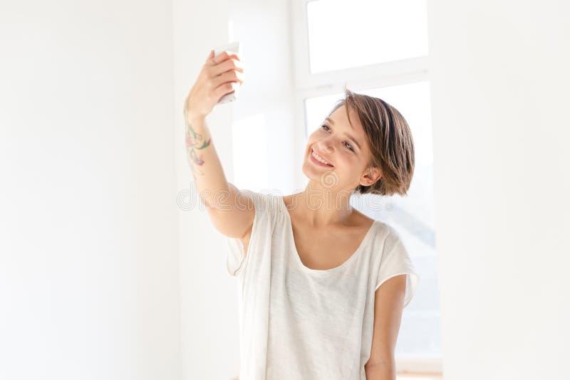 Giovane donna attraente felice con il tatoo che prende selfie immagine stock libera da diritti