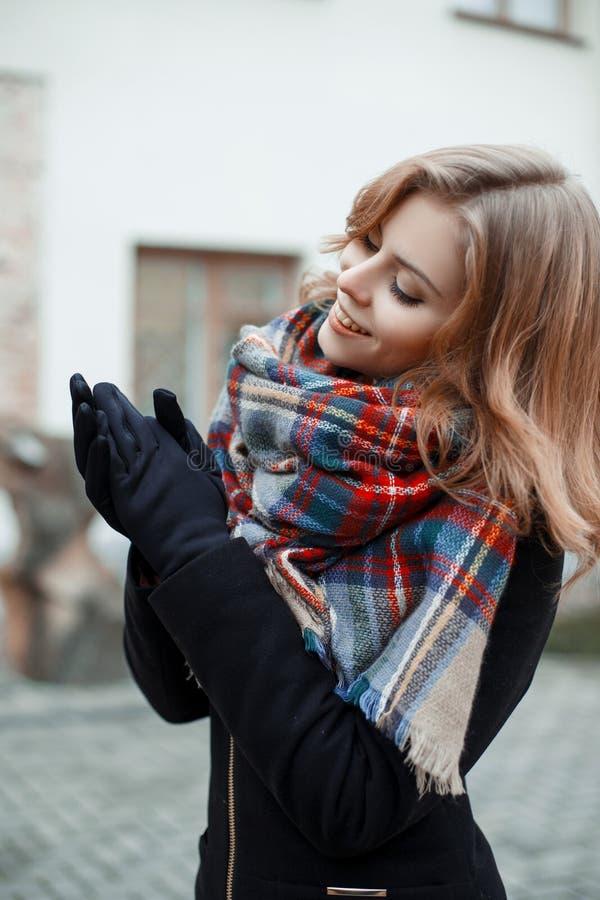 Giovane donna attraente meravigliosa in un cappotto nero alla moda con una sciarpa calda di lana nelle pose nere dei guanti il gi fotografia stock libera da diritti