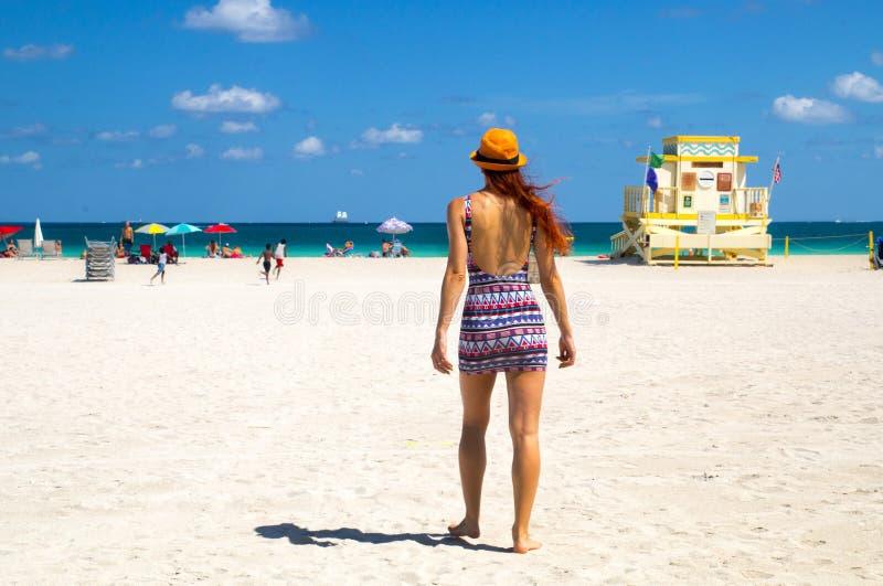 Giovane donna attraente in mini vestito alla moda che cammina verso l'Oceano Atlantico a Miami Beach, Florida, con la torre del b immagini stock