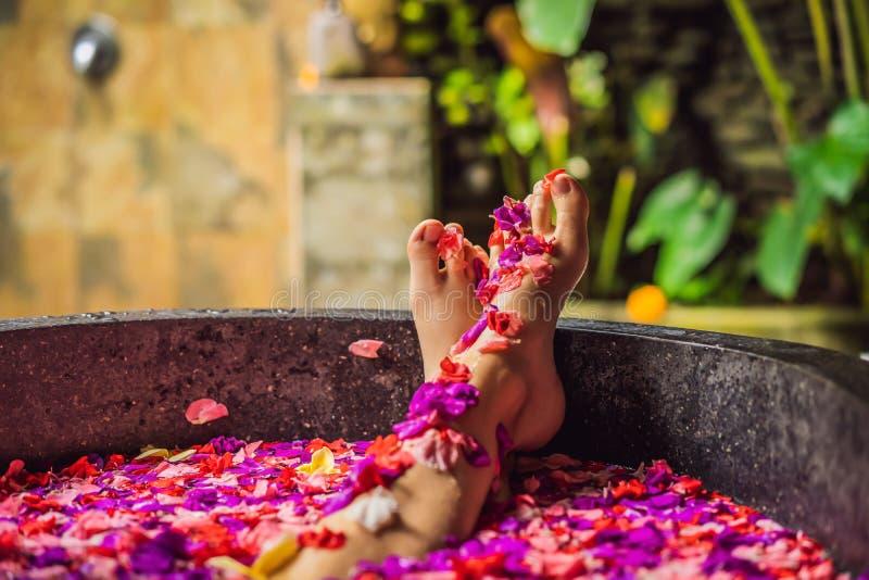 Giovane donna attraente nel bagno con i petali dei fiori e degli oli tropicali dell'aroma Trattamenti della stazione termale per  fotografie stock libere da diritti