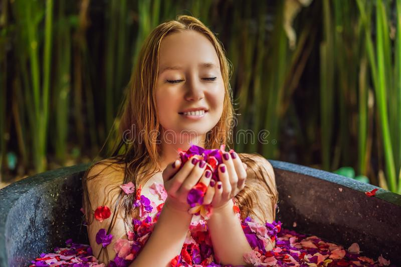 Giovane donna attraente nel bagno con i petali dei fiori e degli oli tropicali dell'aroma Trattamenti della stazione termale per  immagini stock libere da diritti