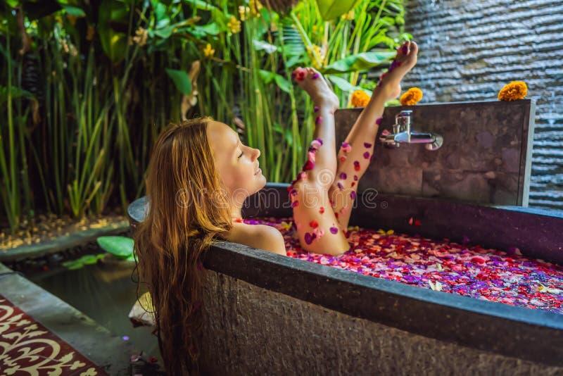 Giovane donna attraente nel bagno con i petali dei fiori e degli oli tropicali dell'aroma Trattamenti della stazione termale per  immagine stock libera da diritti