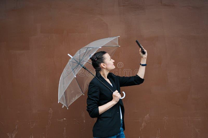 Giovane donna attraente nella posa nera delle blue jeans e del rivestimento all'aperto contro fondo di costruzione fotografie stock libere da diritti