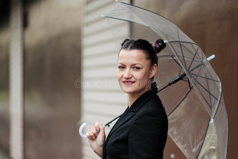Giovane donna attraente nella posa nera delle blue jeans e del rivestimento all'aperto contro fondo di costruzione fotografia stock