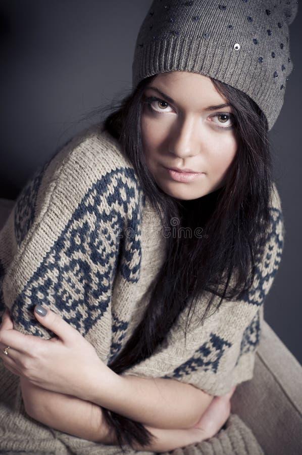 Giovane donna attraente nella seduta accogliente dei vestiti fotografie stock libere da diritti
