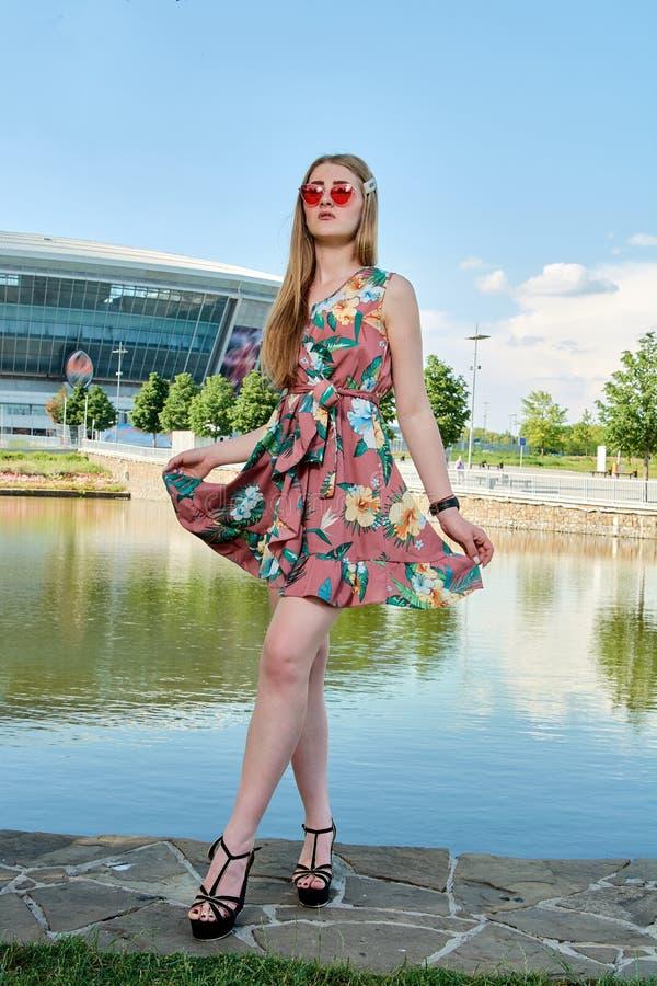 Giovane donna attraente Occhiali da sole rossi, vestito da colore Ritratto del ` s della ragazza Fondo dello stadio di football a immagini stock
