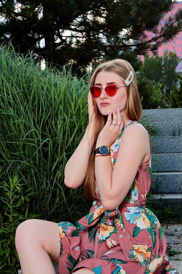 Giovane donna attraente Occhiali da sole rossi, vestito da colore Ritratto della giovane donna fotografia stock libera da diritti