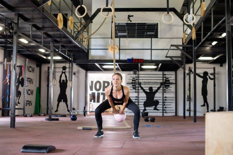Giovane donna attraente in palestra, esercizio con kettlebell immagine stock