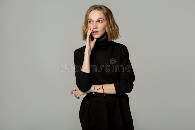 Giovane donna attraente premurosa interessata e disturbata con capelli biondi fotografia stock