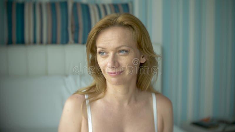 Giovane donna attraente in primo piano bianco di sorrisi della biancheria intima in camera immagini stock