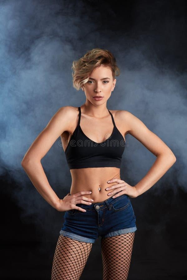 Giovane donna attraente sicura con l'ente perfetto che posa alla macchina fotografica immagini stock libere da diritti