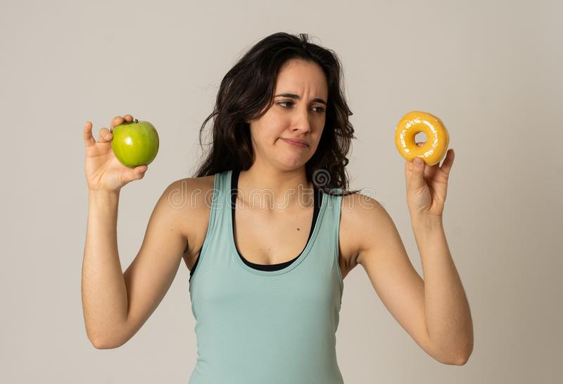 Giovane donna attraente su una dieta che decide fra una mela e una ciambella fotografia stock