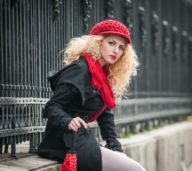 Giovane donna attraente in un colpo di modo di inverno. Bella ragazza con l'ombrello rosso nella via fotografia stock