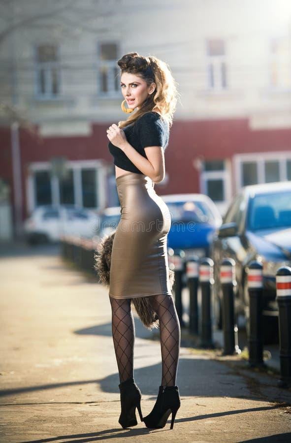 Giovane donna attraente in un colpo urbano di modo. Bella ragazza alla moda con i vestiti aderenti e la posa lunga delle gambe immagini stock