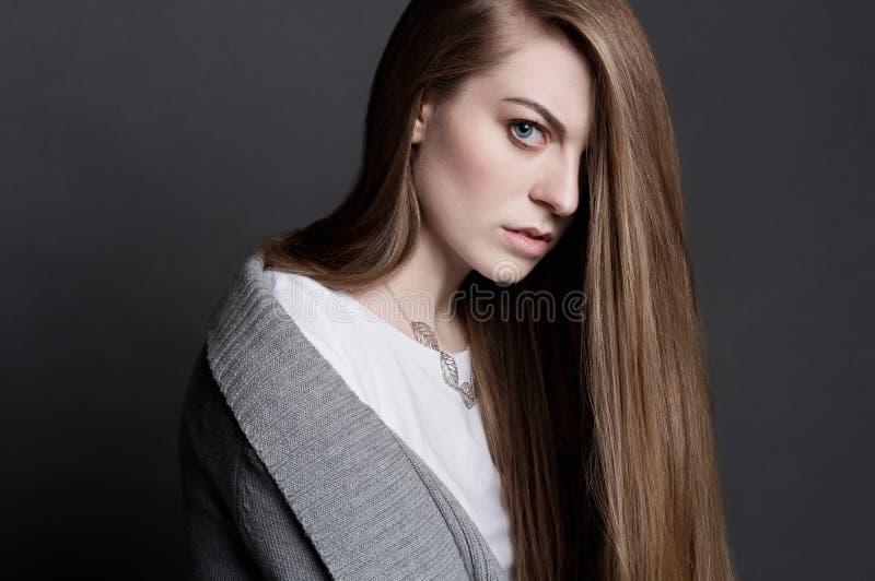 Giovane donna attraente in un maglione grigio ed in una maglietta bianca fotografie stock