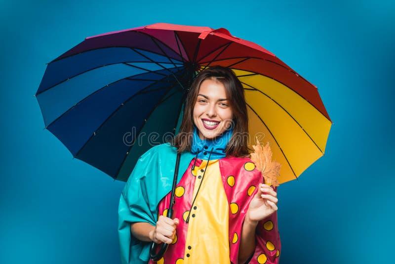 Giovane donna attraente in vestiti stagionali con la foglia dorata L'umore di autunno ed il tempo sono caldi e soleggiati e piogg fotografia stock