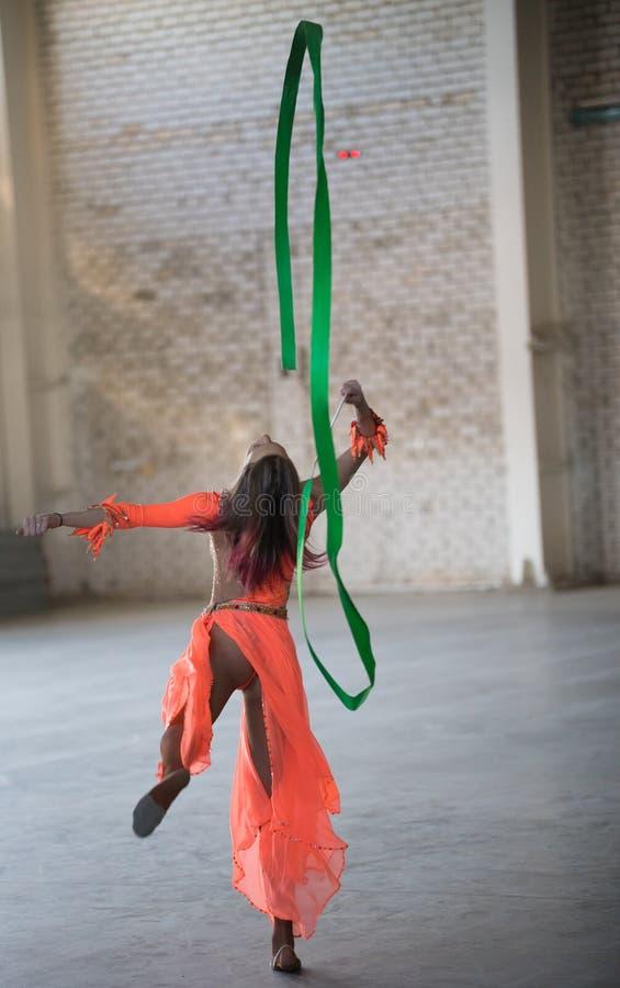 Giovane donna attraente in vestito arancio che balla con il nastro relativo alla ginnastica in mani nel magazzino fotografia stock