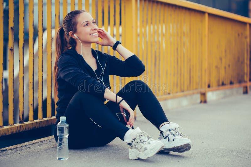 Giovane donna in attrezzatura nera di sport che prende rottura dopo avere corso sul ponte fotografia stock libera da diritti