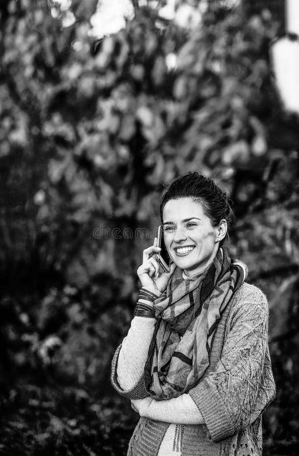 Giovane donna in autunno che uguaglia telefono cellulare all'aperto di conversazione immagine stock libera da diritti