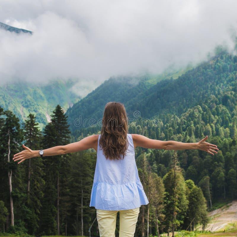 Giovane donna bella che sta sulla collina della montagna fotografia stock libera da diritti