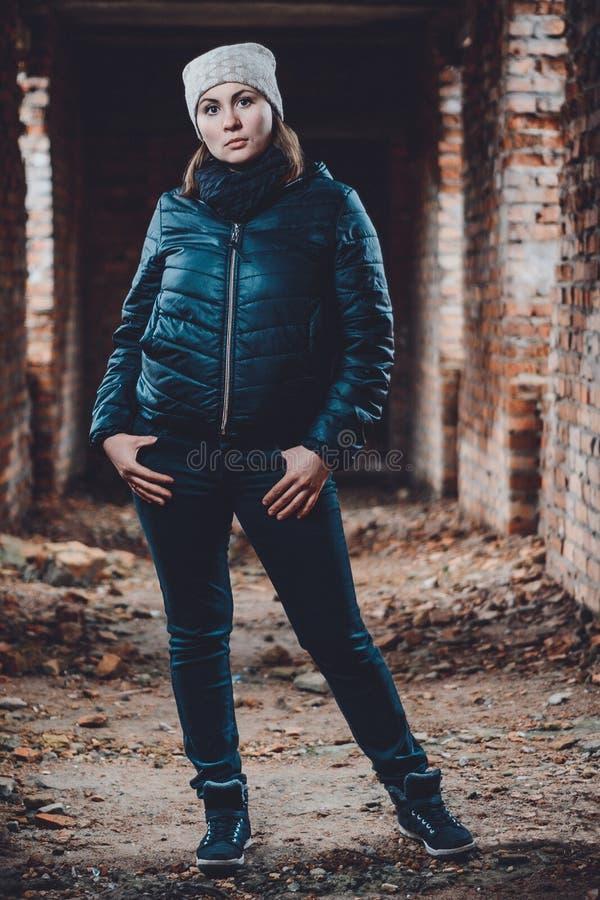 Giovane donna bella che sta in una costruzione distrutta nell'annegamento freddo immagini stock