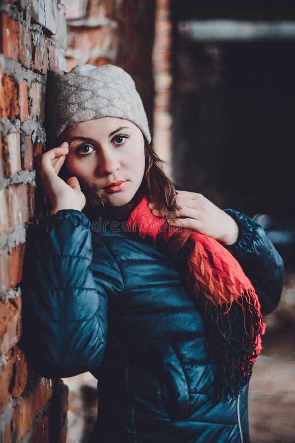 Giovane donna bella che sta in una costruzione distrutta nell'annegamento freddo immagine stock libera da diritti