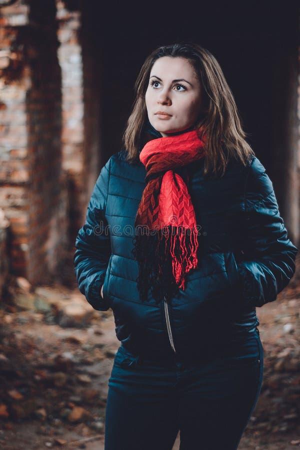 Giovane donna bella che sta in una costruzione distrutta nell'annegamento freddo fotografia stock libera da diritti