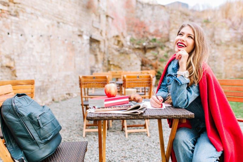 Giovane donna bella di risata che scrive poesia nel cortile enorme durante la mattina Ragazza allegra con un capo rosso fotografie stock libere da diritti