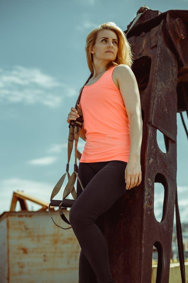 Giovane donna bella in una maglietta arancio con le cinghie di forma fisica del trx immagine stock