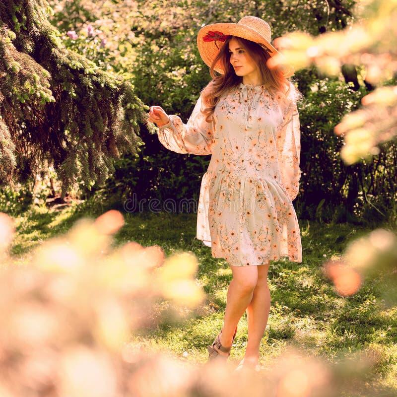 Giovane donna bellissima che danza nel parco Cappello e abbigliamento estivo leggero immagine stock libera da diritti